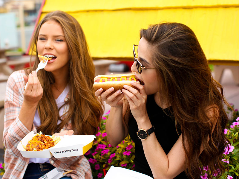 Wienerschnitzel Customers enjoying Hot Dogs